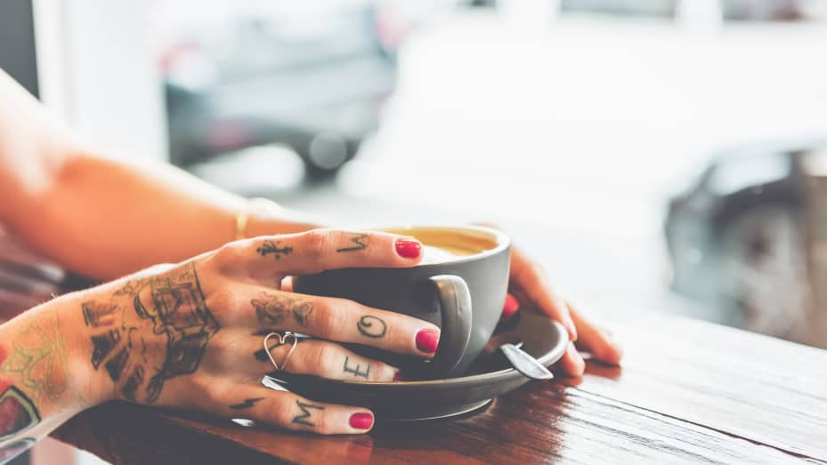 A woman with tattoos drinks coffee in a Melbourne cafe.