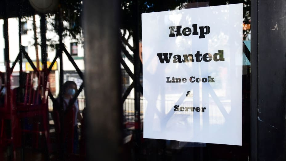 """Pedestrians walk past a """"Help Wanted"""" sign posted at restaurant looking for line cooks and servers on June 22, 2021 in Los Angeles."""