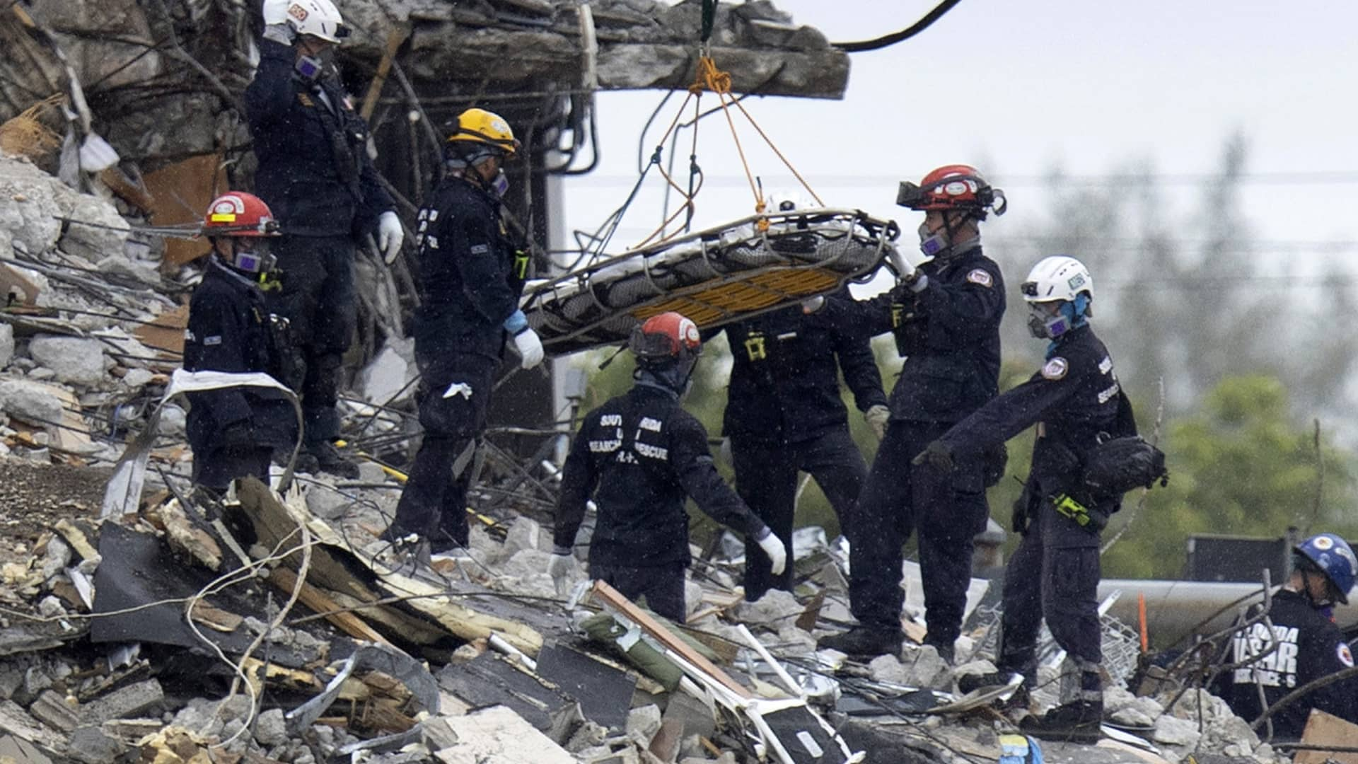 Search and Rescue personnel remove a stretcher from the rubble of the partially collapsed 12-story Champlain Towers South condo building on June 28, 2021 in Surfside, Florida.