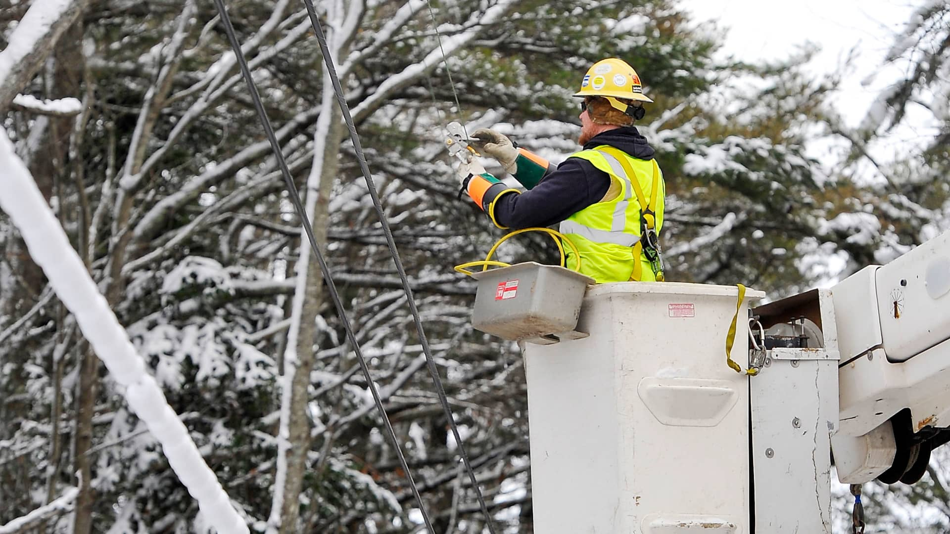 A line worker for Evergreen Electric, applies protective grounds to lines to protect other electrical workers who are repairing nearby lines in Harpswell, Maine.