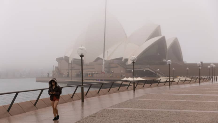 A person exercises at the Sydney Opera House during a foggy start to the day on June 30, 2021 in Sydney, Australia.