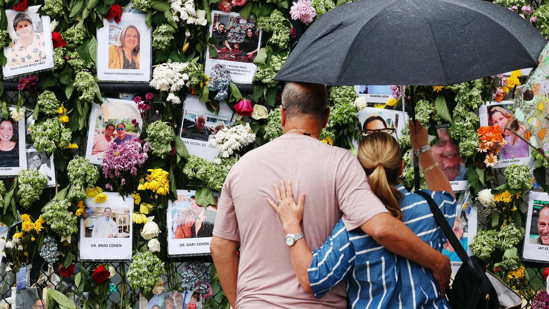 People look at a memorial that has pictures of some of the missing from the partially collapsed 12-story Champlain Towers South condo building on June 30, 2021 in Surfside, Florida.