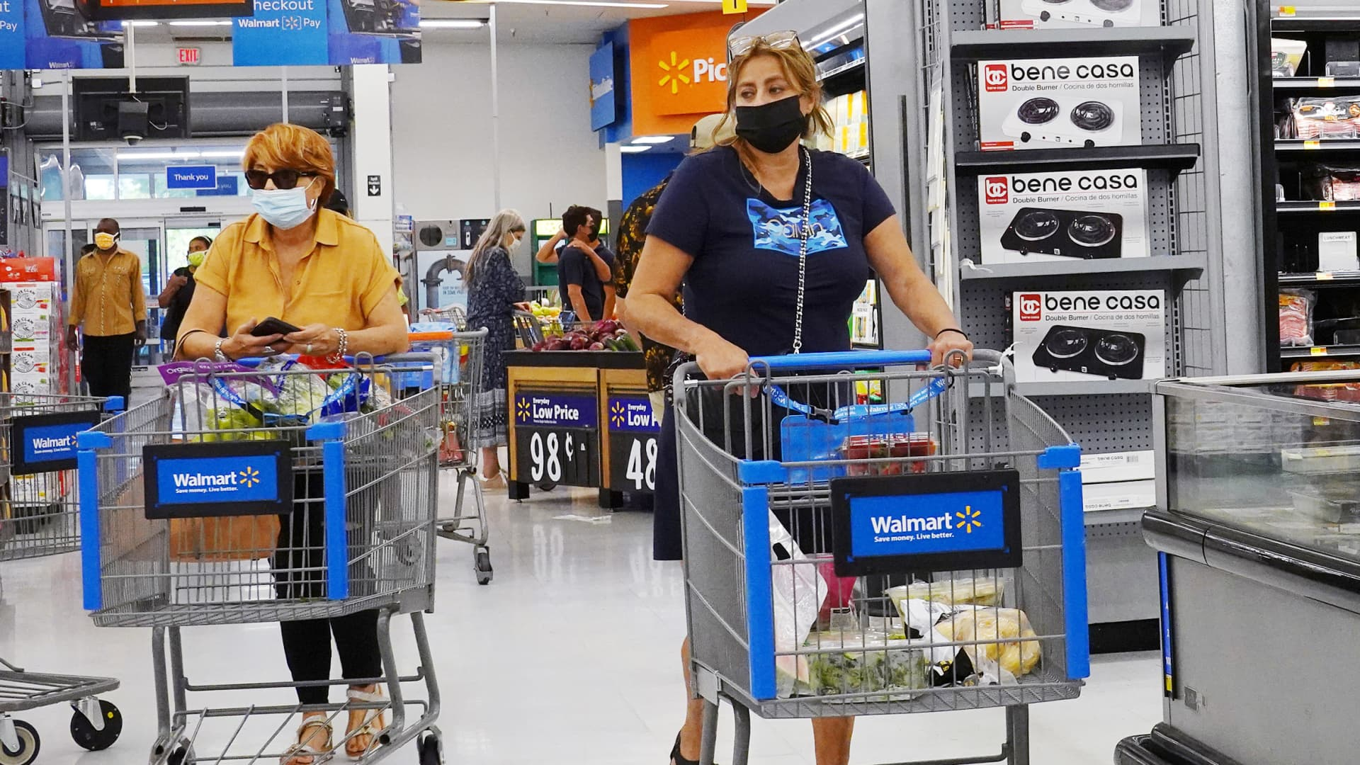 People wearing protective masks shop in a Walmart store on May 18, 2021 in Hallandale Beach, Florida.
