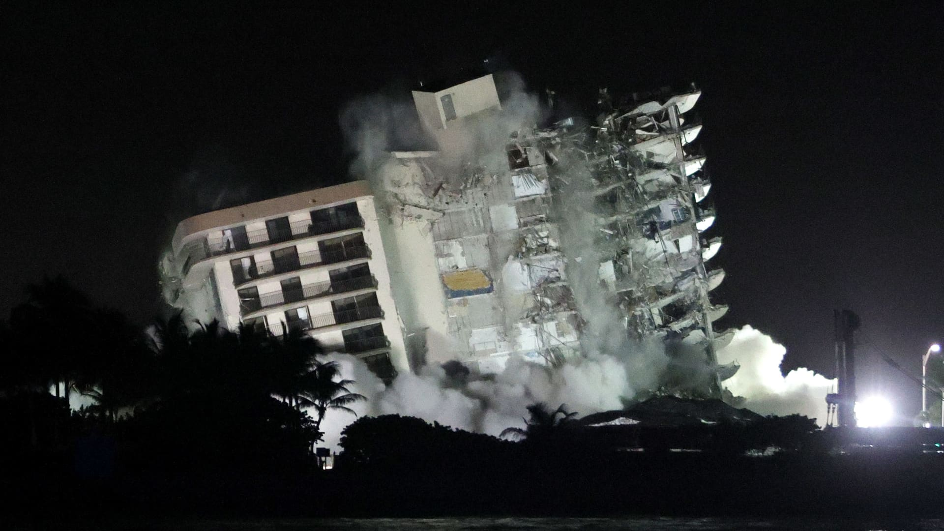 The remaining part of the partially collapsed 12-story Champlain Towers South condo building falls in a controlled demolition on July 4, 2021 in Surfside, Florida.