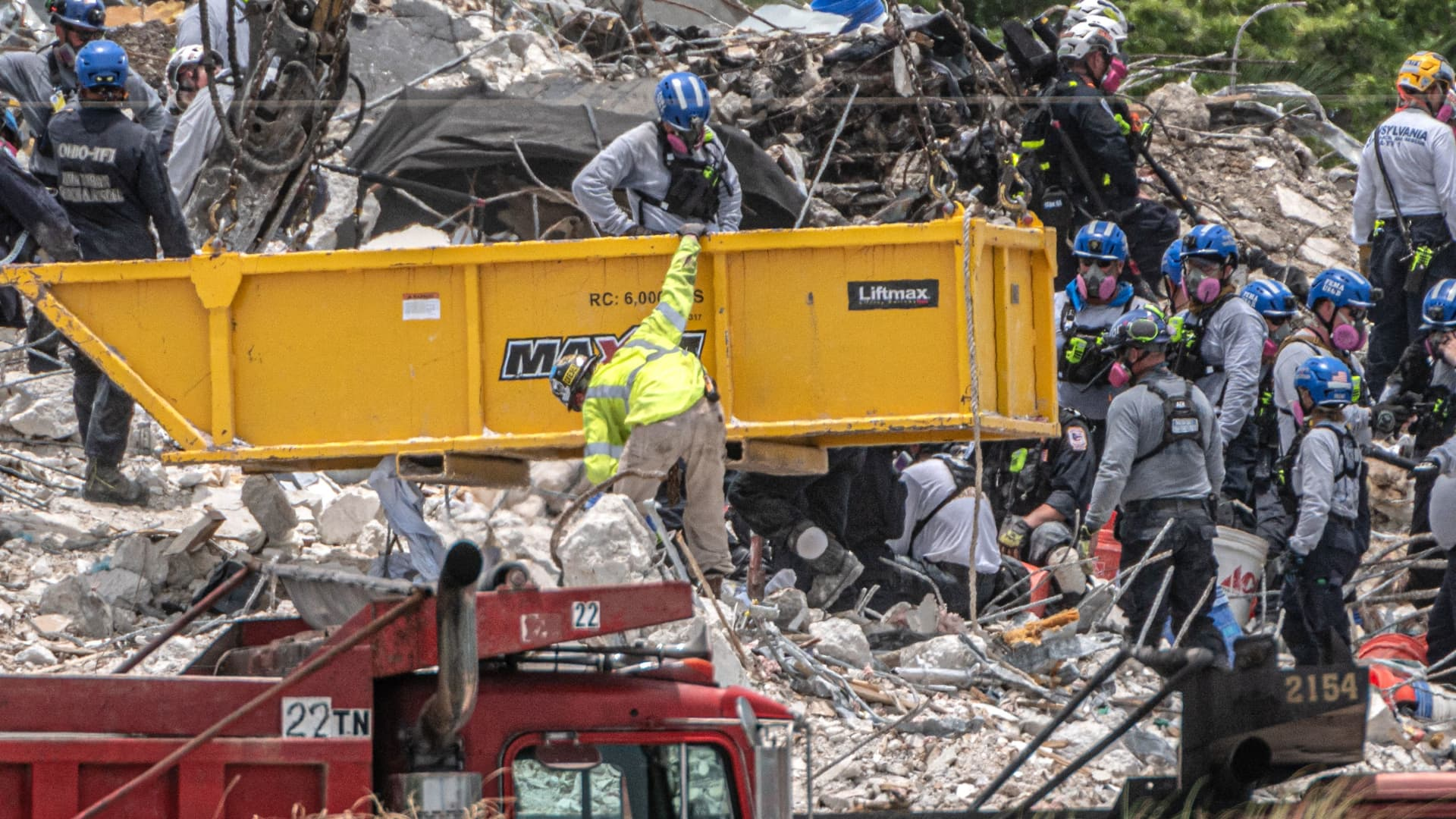 After a brief stop to demolish the standing debris, Search and Rescue personnel continue working in the rubble pile of the partially collapsed 12-story Champlain Towers South condo on July 5, 2021 in Surfside, Florida.