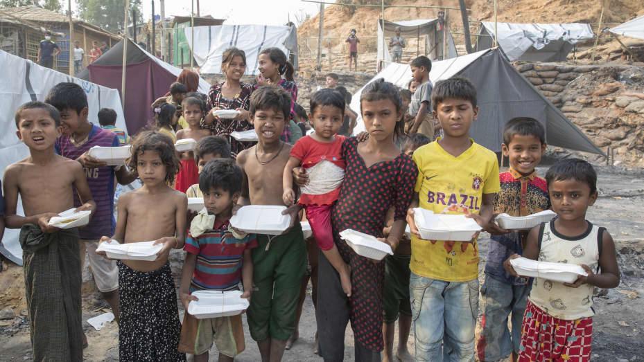Trẻ em được nhìn thấy đang lấy thức ăn do các tổ chức phi chính phủ và tổ chức xã hội cung cấp, sau vụ hỏa hoạn tại một trại tị nạn ở Ukhia, thuộc quận Cox's Bazar, đông nam nước này vào ngày 24 tháng 3 năm 2021.