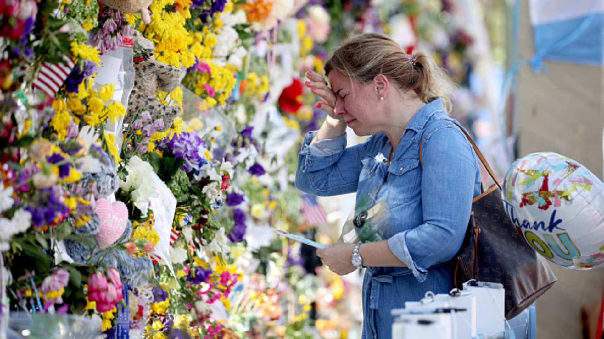 Laura Solla weeps as she places flowers near the memorial site for victims of the collapsed 12-story Champlain Towers South condo building on July 08, 2021 in Surfside, Florida.
