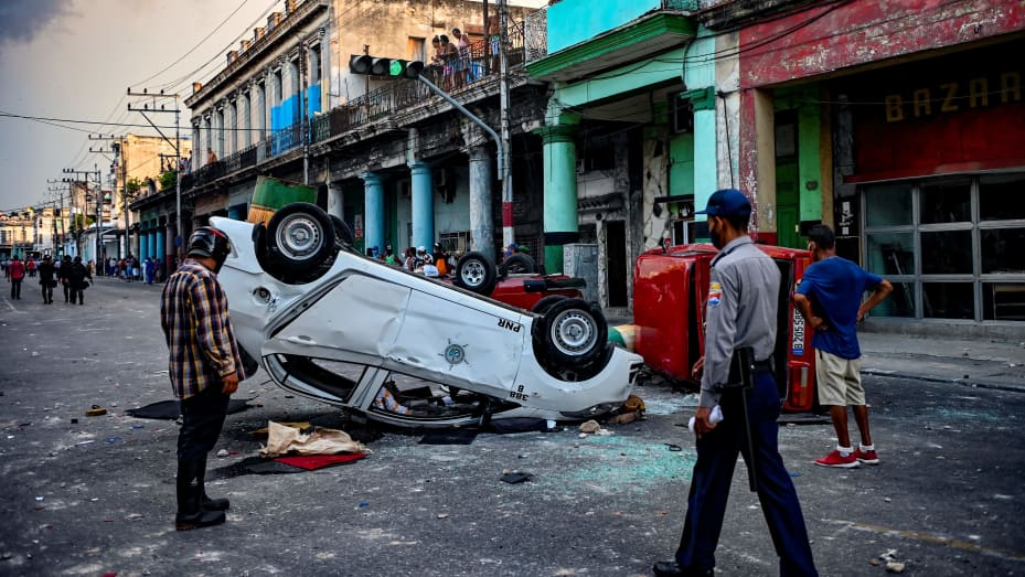Police cars are seen overturned in the street in the framework of a demonstration against Cuban President Miguel Diaz-Canel in Havana, on July 11, 2021.