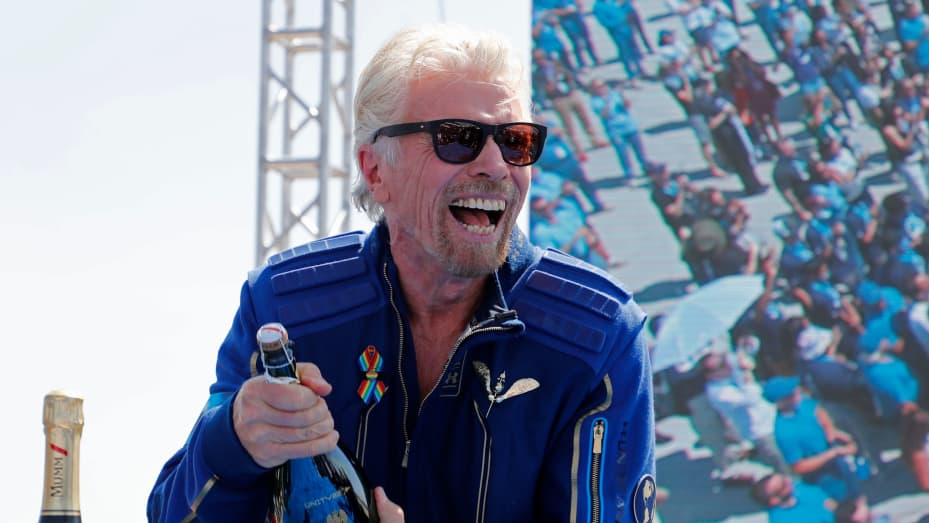 Billionaire entrepreneur Richard Branson prepares to spray champagne after flying with a crew in Virgin Galactic's passenger rocket plane VSS Unity to the edge of space at Spaceport America near Truth or Consequences, New Mexico, U.S., July 11, 2021.