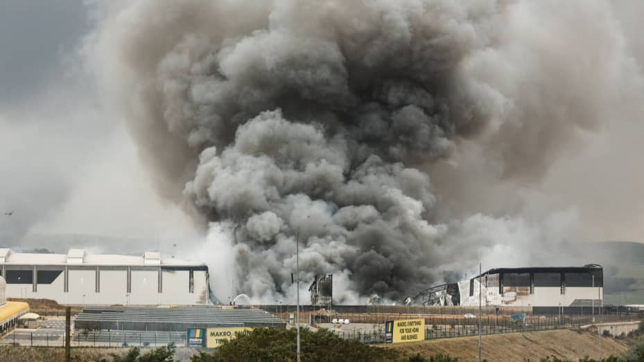 Smoke rises from a Makro building set on fire overnight in Umhlanga, north of Durban, on July 13, 2021 as several shops, businesses and infrastructure are damaged in the city, following four nights of continued violence and looting sparked by the jailing
