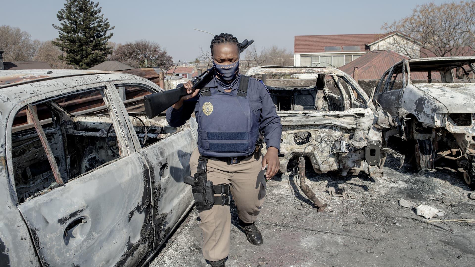 A Johannesburg Metro Police Department (JMPD) officer walks between burnt cars at a car showroom in Jeppestown, Johannesburg, on July 11, 2021.