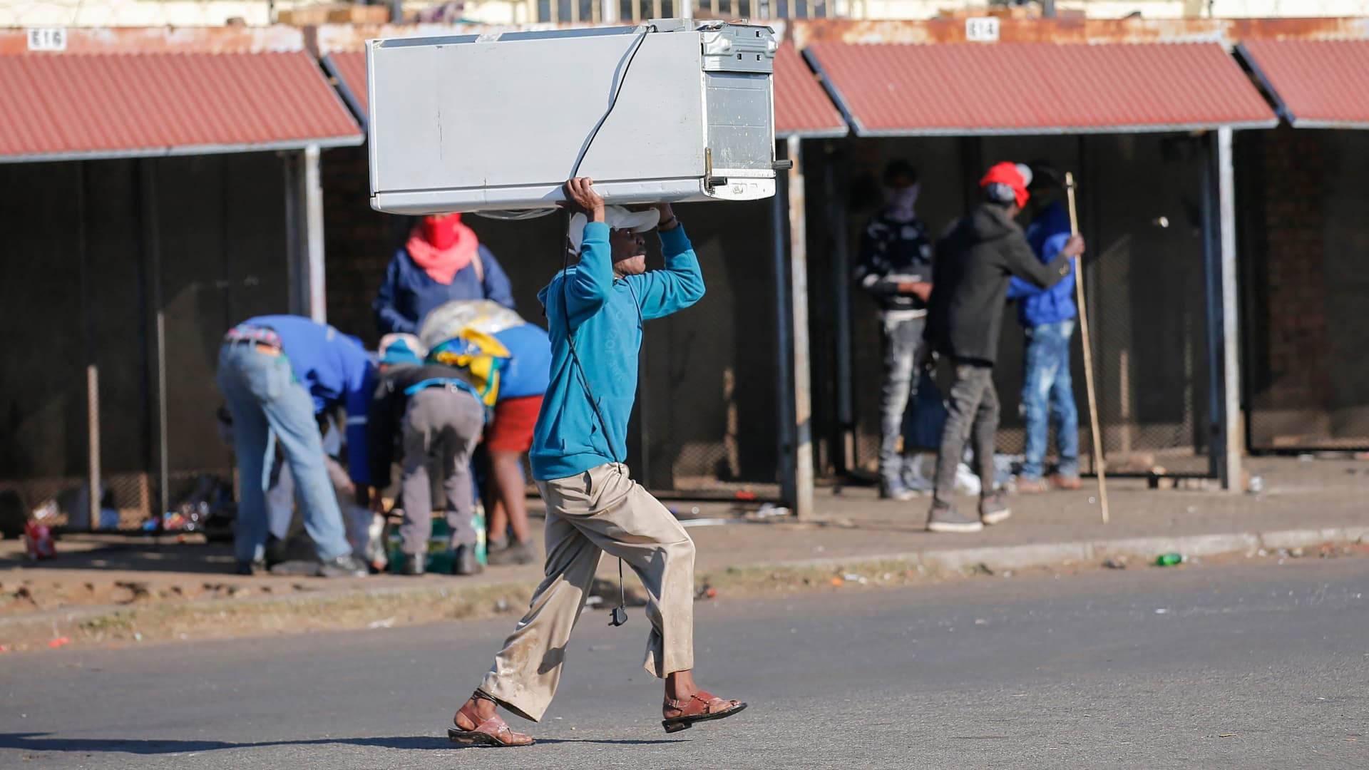 A man carries a fridge on his head that was looted from the Lotsoho Mall in Katlehong township, East of Johannesburg, on July 12, 2021.