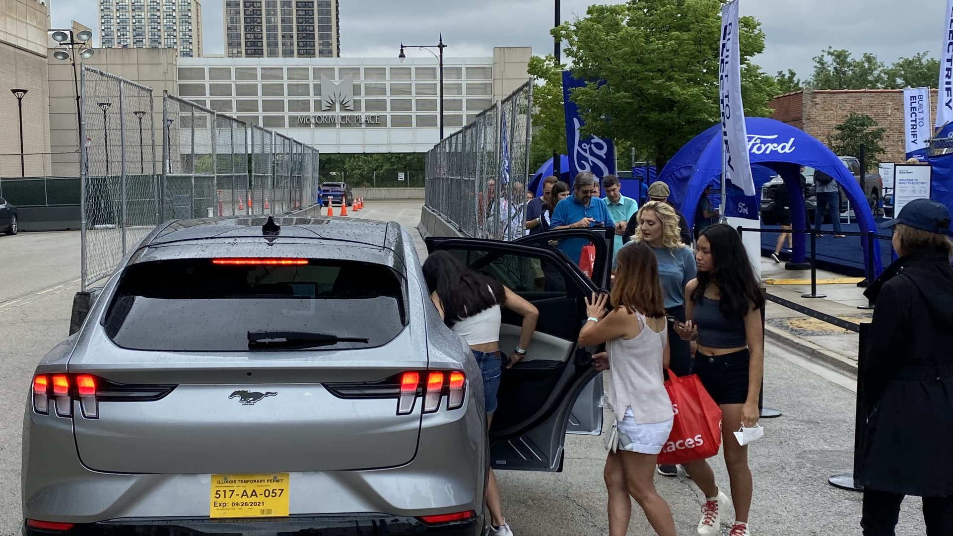 Attendees of the Chicago Auto Show on July 15, 2021 get into a Ford Mustang Mach-E for a test ride in the electric crossover outside of the McCormick Place Convention Center.