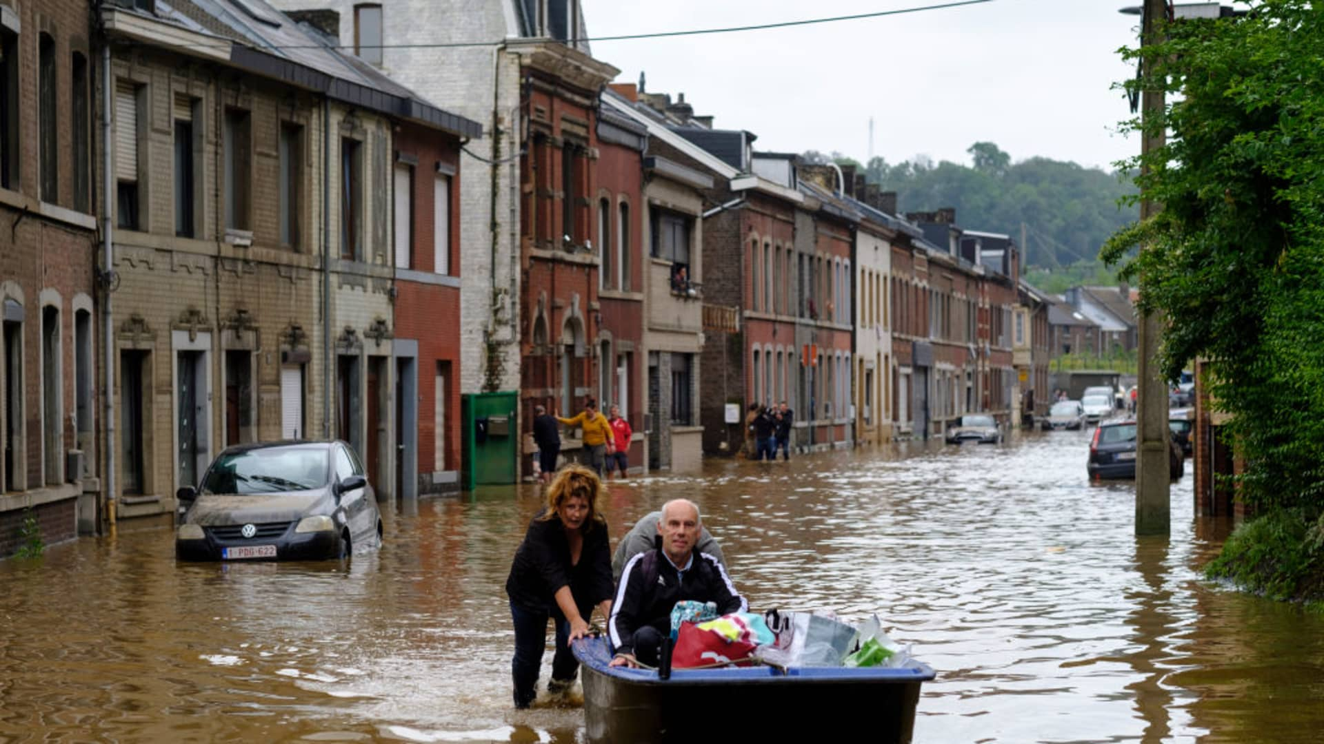 ANGLEUR, LIEGE, BELGIUM - JULY 16: People use a boat to bring man out of home following a severe storm on July 16, 2021 in 'Rue de Tilff' in Angleur, a district from Liège, Belgium.