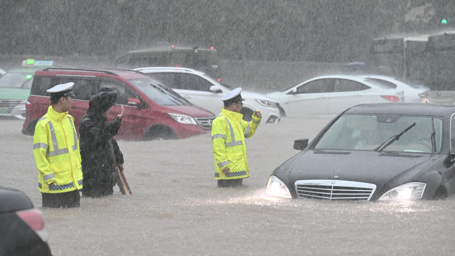 Policemen evacuate traffic in floodwater near Zhengzhou Railway Station on July 20, 2021 in Zhengzhou, Henan Province of China.