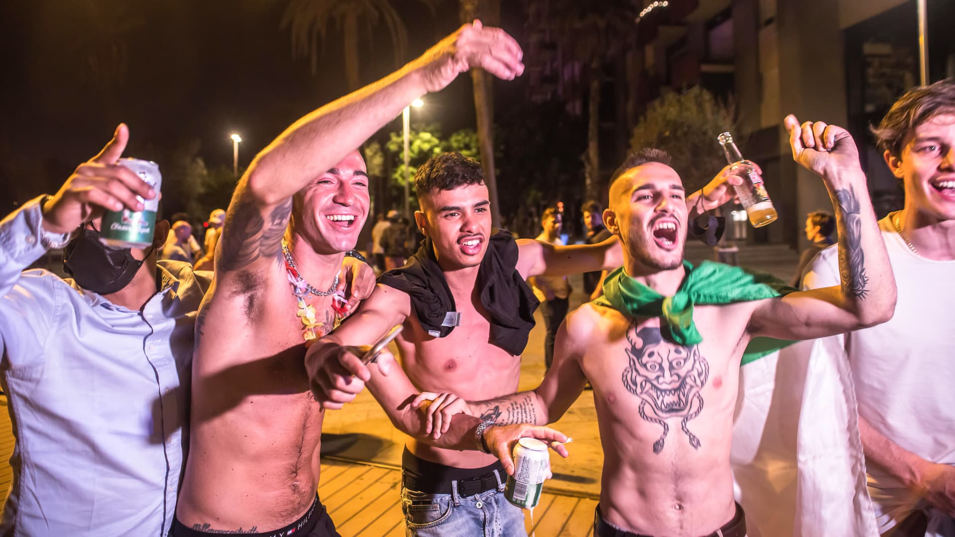 Young men with alcohol drinks in their hands make fun and shout on Barceloneta beach promenade on July 17 2021. Police evicts crowds from Barceloneta beach after Catalonia decreed the return of a 1am curfew given the rebound in Covid-19 cases as a result of the delta variant of the coronavirus.