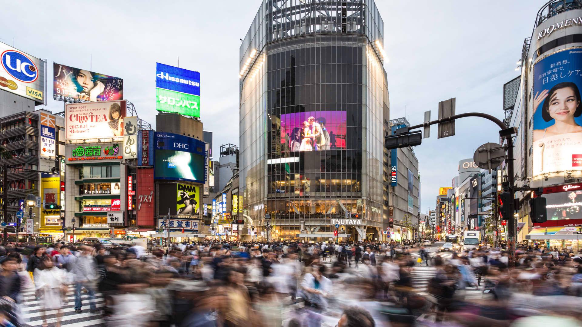 Crowds walk through Shibuya Crossing in Tokyo, Japan.