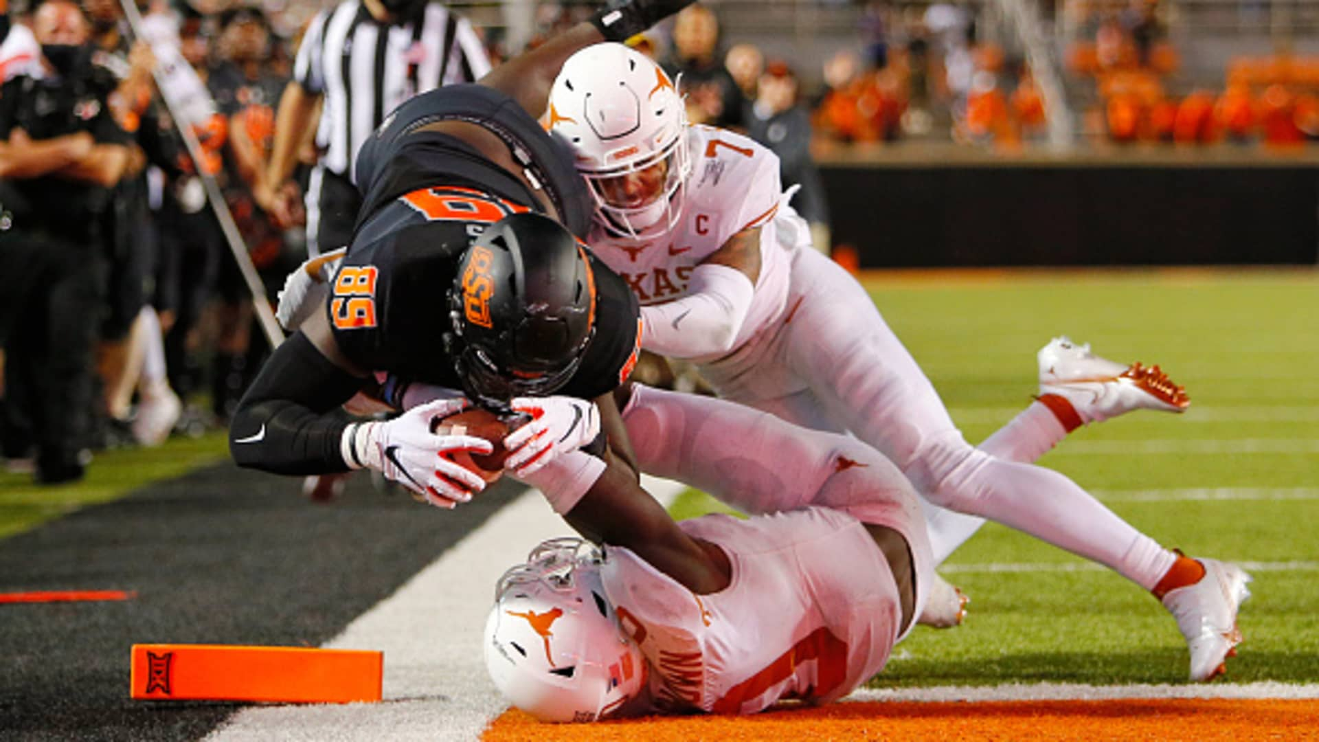 Tight end Jelani Woods #89 of the Oklahoma State Cowboys dives into the end zone for a nullified overtime touchdown against defensive back Caden Sterns #7 and linebacker DeMarvion Overshown #0 of the Texas Longhorns at Boone Pickens Stadium on October 31, 2020 in Stillwater, Oklahoma.