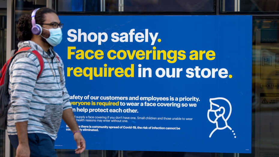 """A man wearing a mask walks past a """"shop safely as the city continues , face covers are required in our store"""" sign outside a Best Buy in Union Square Phase 4 of re-opening following restrictions imposed to slow the spread of coronavirus on September 30, 2"""