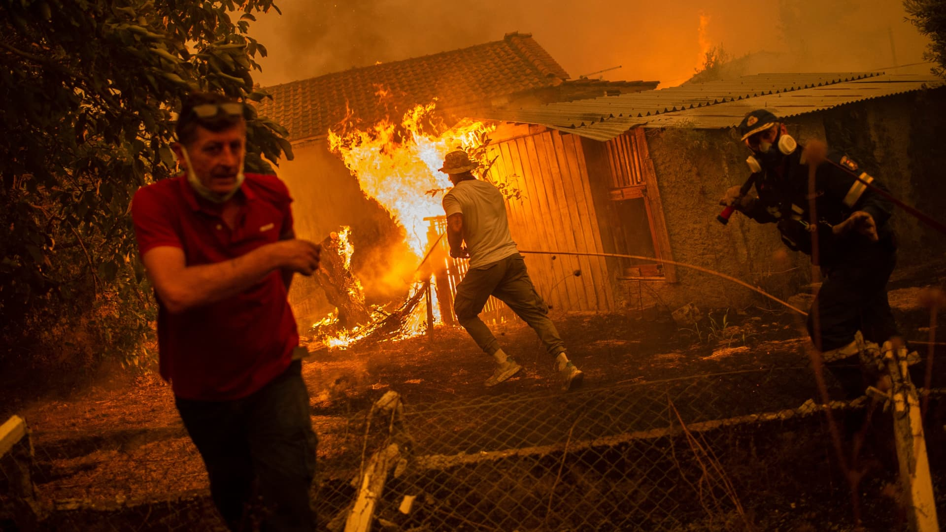 A firefighter and locals rush to a burning house in an attempt to extinguish forest fires that are approaching the village of Pefki on Evia (Euboea) island on August 8, 2021.