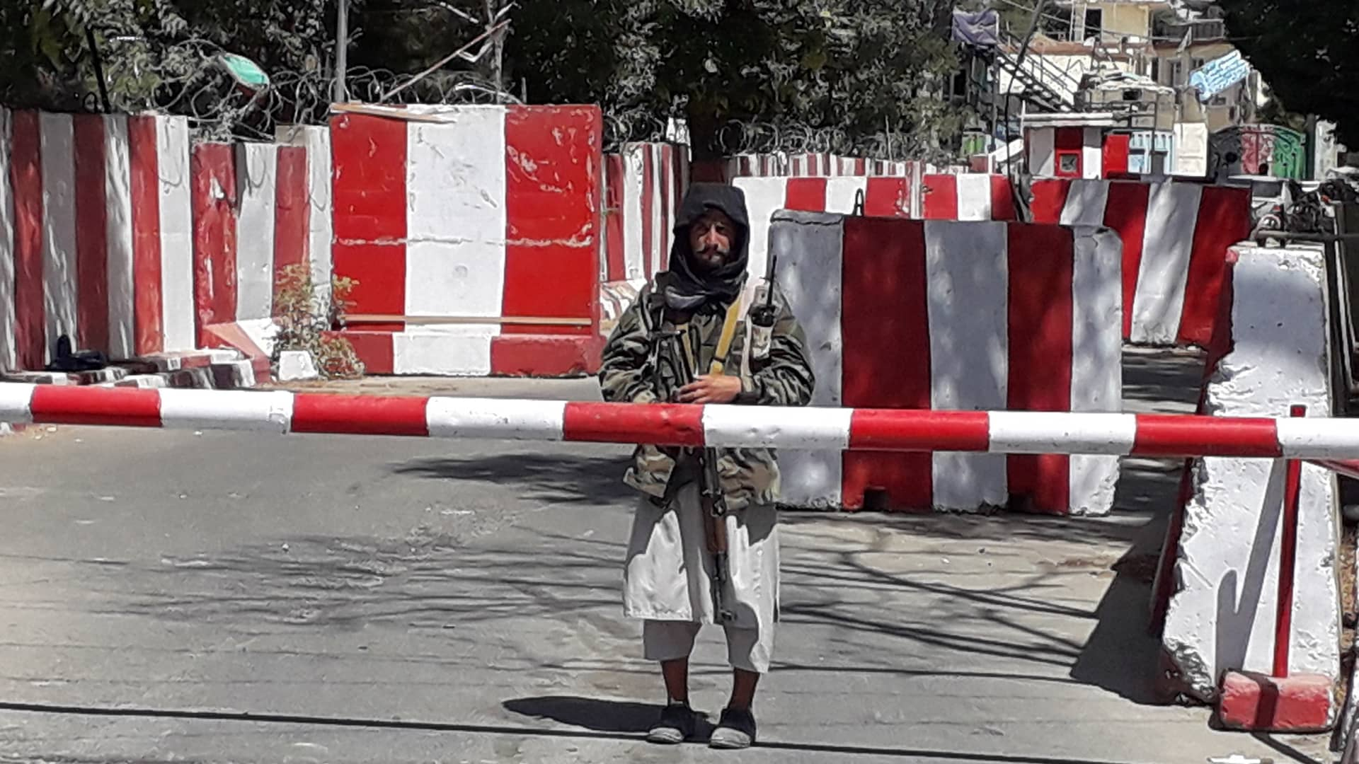 A Taliban fighter stands guard at the entrance of the police headquarters in Ghazni on August 12, 2021, as Taliban move closer to Afghan capital after taking Ghazni city.