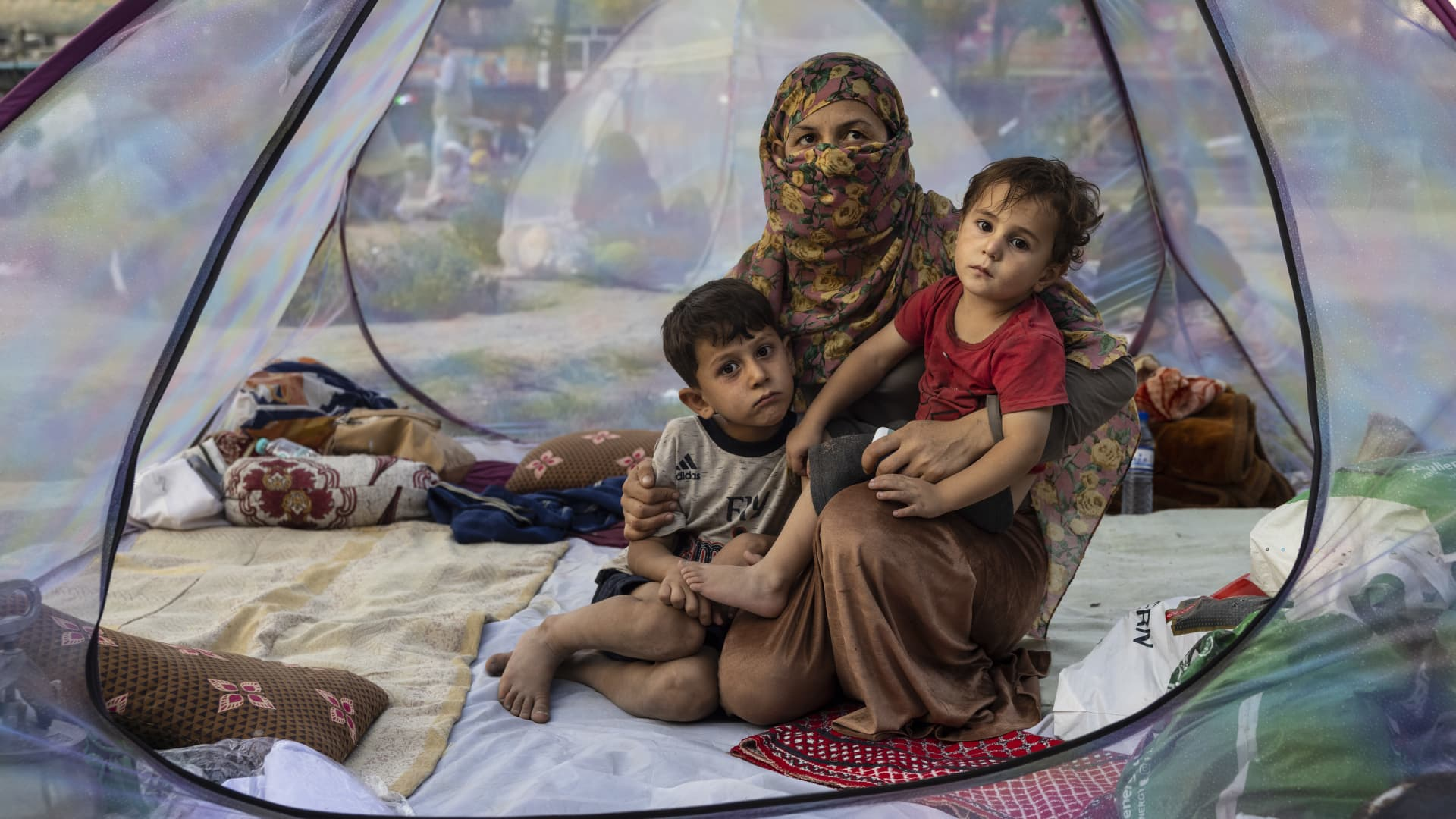 Farzia, 28, who lost her husband in Baghlan one week ago to fighting by the Taliban sits with her children, Subhan, 5, and Ismael ,2, in a tent at a makeshift IDP camp in Share-e-Naw park to various mosques and schools on August 12, 2021 in Kabul, Afghanistan.