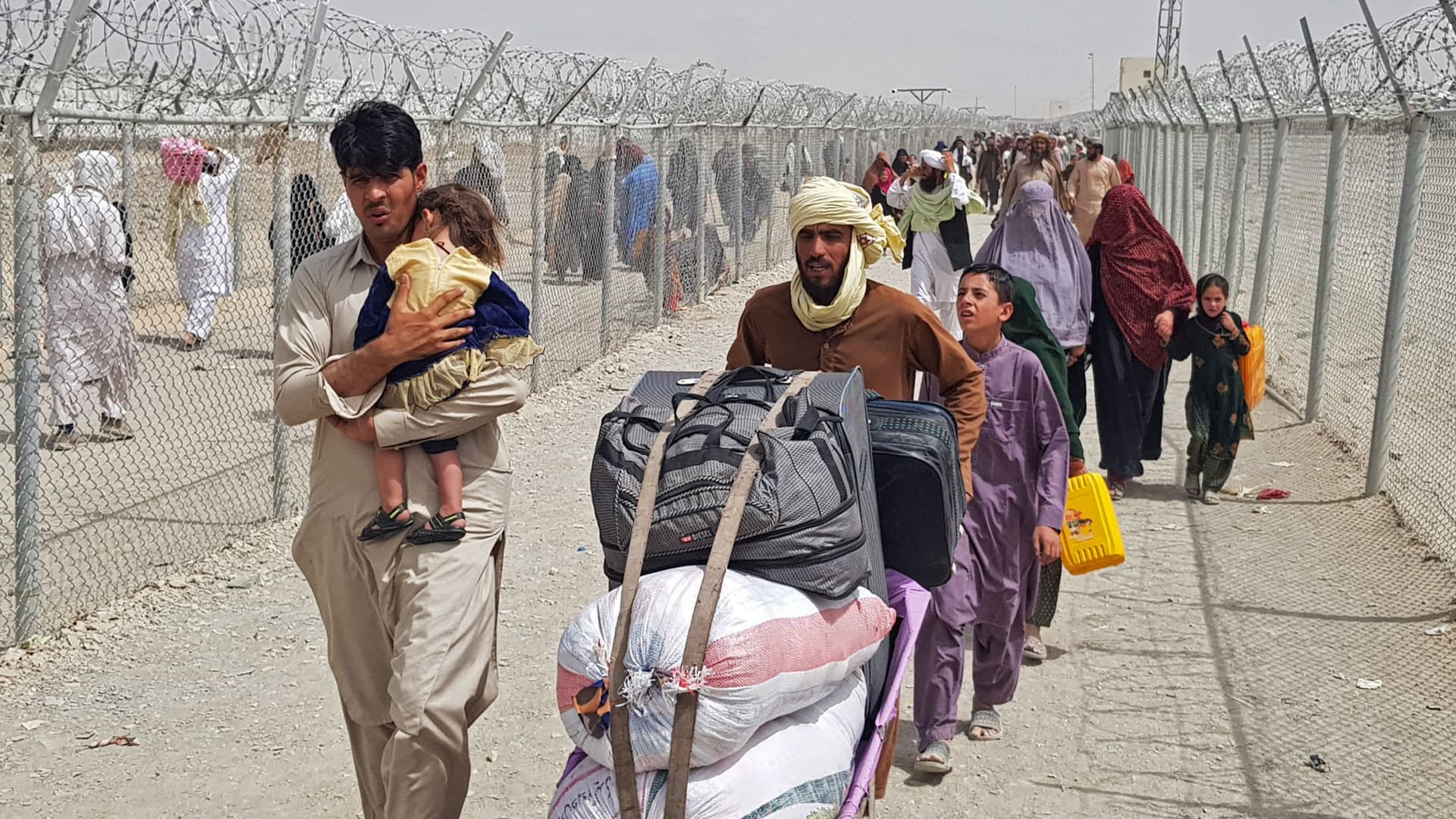 Stranded Afghan nationals arrive to return back to Afghanistan at the Pakistan-Afghanistan border crossing point in Chaman on August 16, 2021 as the Taliban were in control of Afghanistan after President Ashraf Ghani fled the country and conceded the insurgents had won the 20-year war.