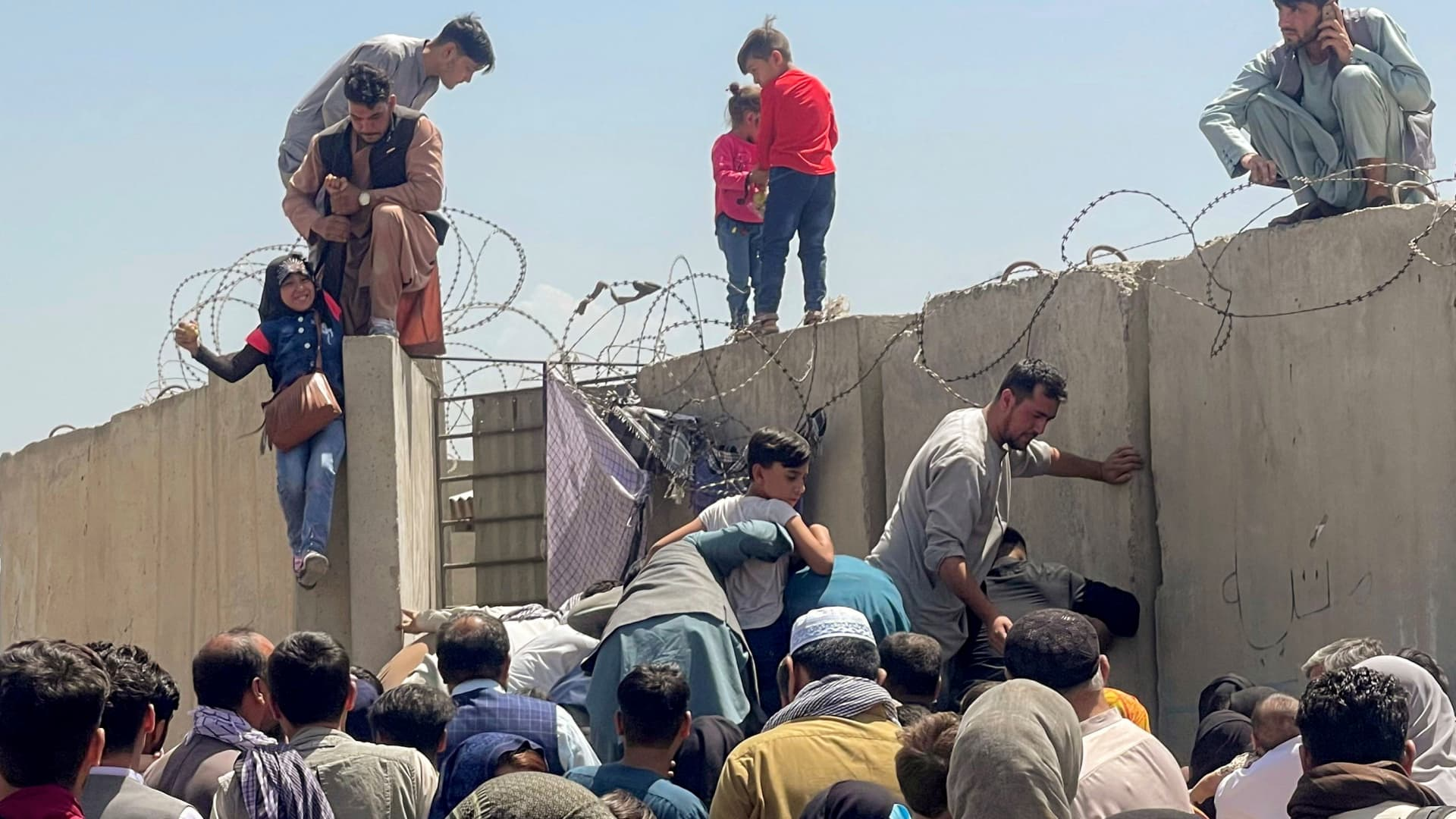 A man pulls a girl to get inside Hamid Karzai International Airport in Kabul, Afghanistan August 16, 2021.