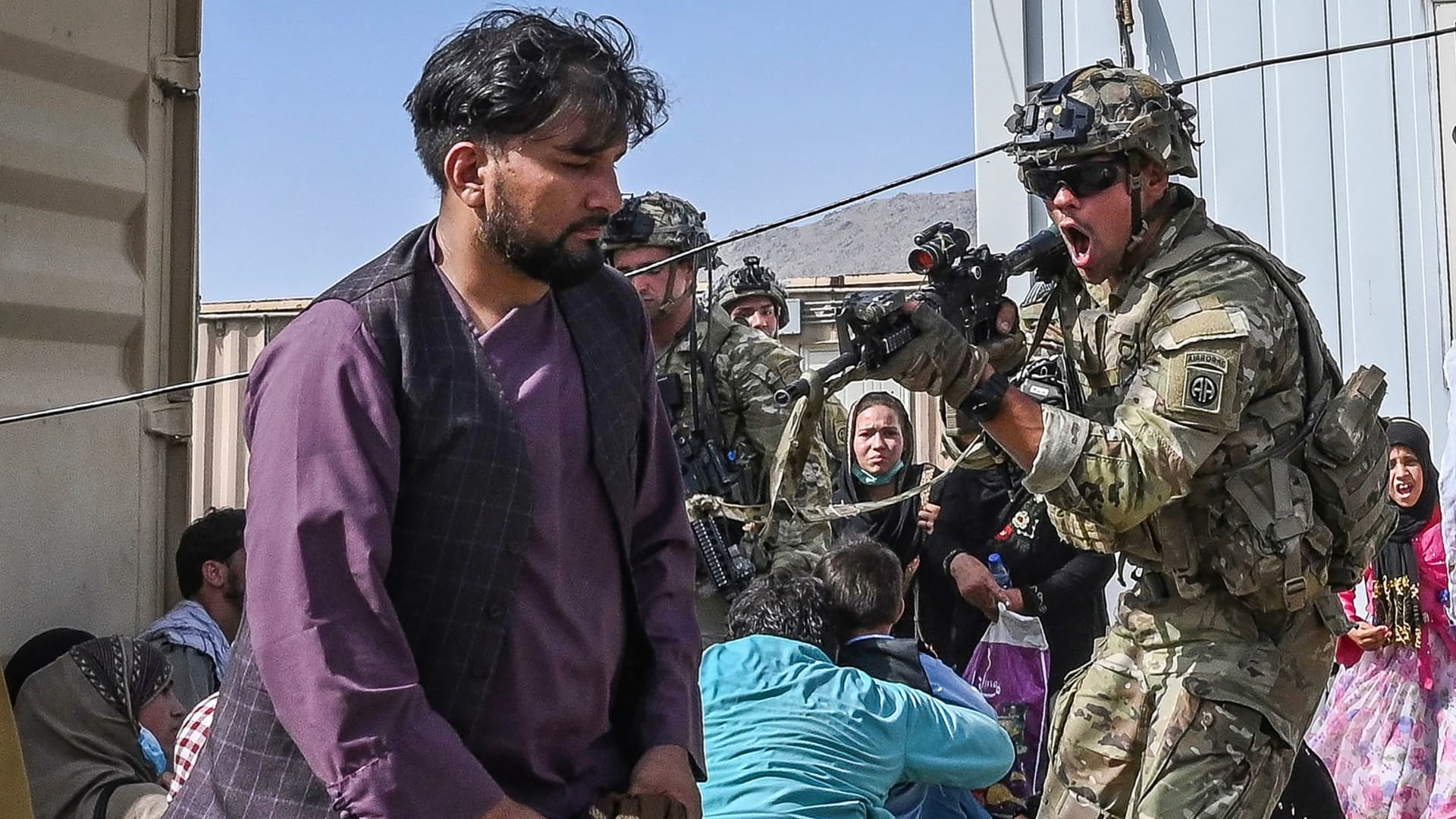 A US soldier (C) point his gun towards an Afghan passenger at the Kabul airport in Kabul on August 16, 2021, after a stunningly swift end to Afghanistan's 20-year war, as thousands of people mobbed the city's airport trying to flee the group's feared hardline brand of Islamist rule.