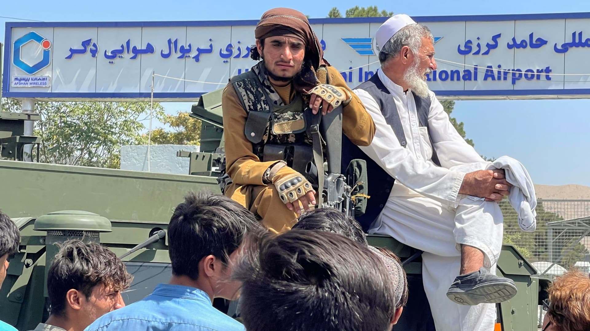 A member of Taliban forces (L) sits on a an armoured vehicle outside Hamid Karzai International Airport in Kabul, Afghanistan August 16, 2021.