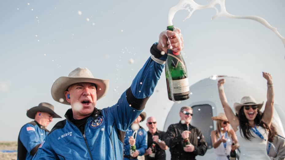 Jeff Bezos pops champagne after emerging from the New Shepard capsule after his spaceflight on July 20, 2021.