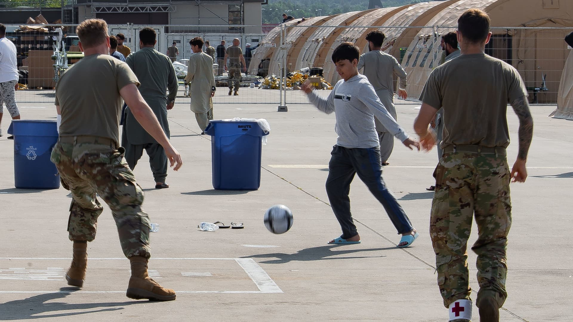 U.S. Air Force airmen play soccer with Afghan evacuees at Ramstein Air Base in Germany on Aug. 21, 2021.