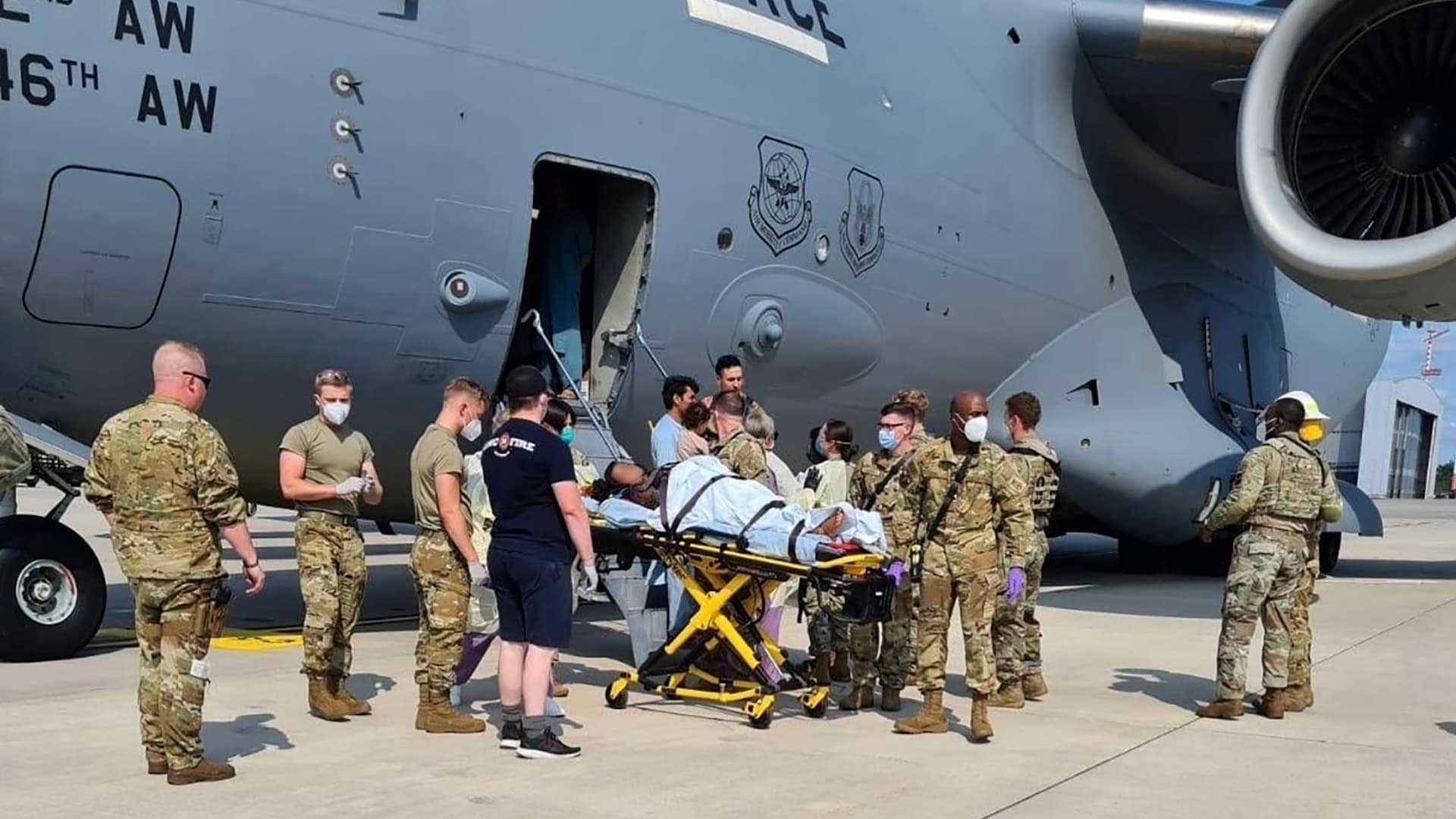 Medical support personnel help an Afghan mother, whose identity has been digitally obscured at the source, with her family off a U.S. Air Force C-17 at Ramstein Air Base in Germany moments after she delivered a baby aboard the aircraft on Aug. 21, 2021.