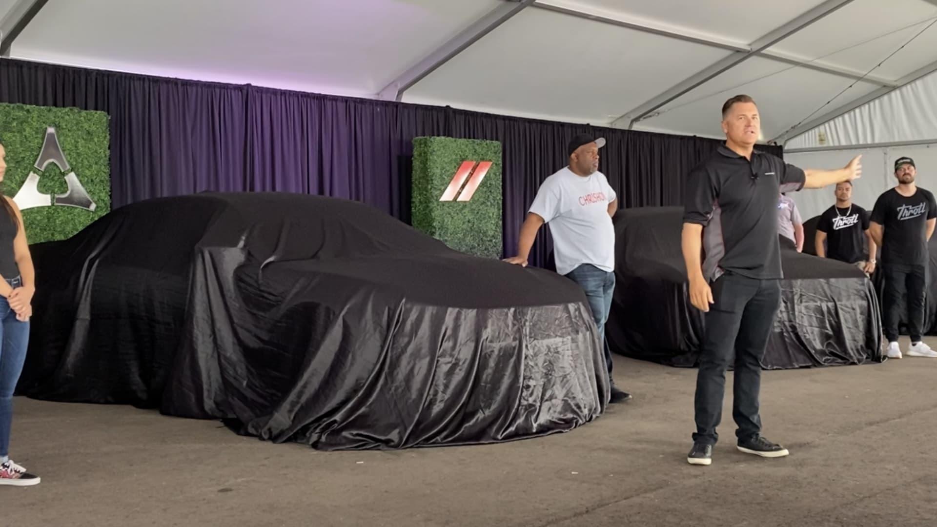 Dodge CEO Tim Kuniskis speaks Aug. 13, 2021 during a media event. In the back, the Fratzog logo was used alongside Dodge's current logo.