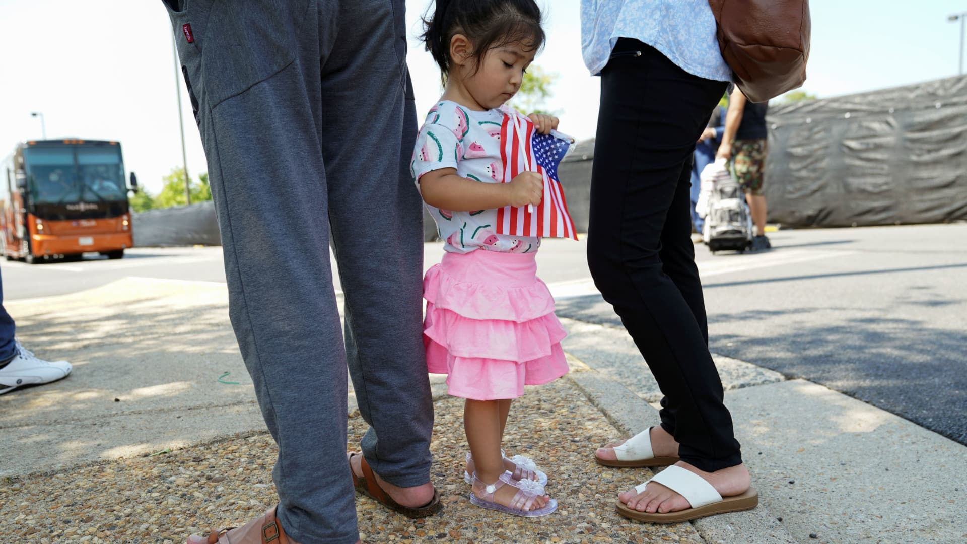 An Afghan girl holding a U.S. flag waits with her parents for relatives at a processing center for evacuees from Afghanistan near Dulles International Airport on Aug. 24, 2021.