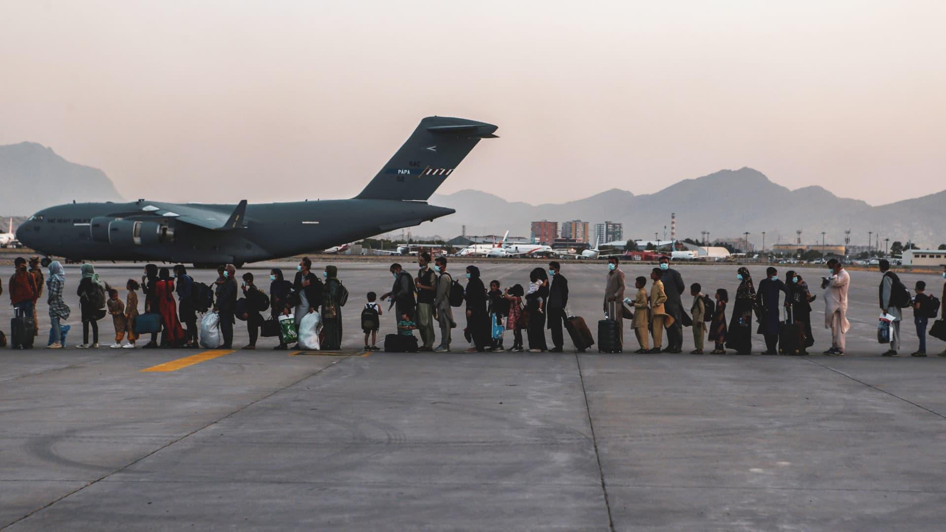 Evacuees wait to board a Boeing C-17 Globemaster III during an evacuation at Hamid Karzai International Airport in Kabul, Afghanistan, August 23, 2021.