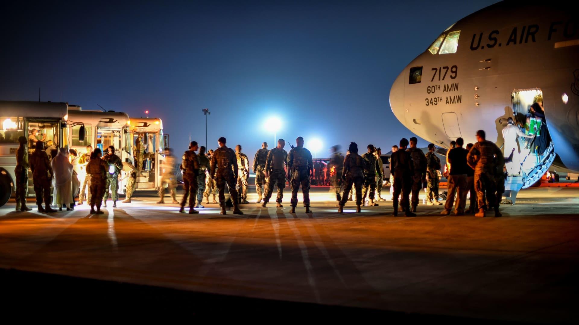 Afghan evacuees leave a U.S. Air Force C-17 cargo plane after arriving at Ali Al Salem Air Base in Kuwait on Aug. 24, 2021.
