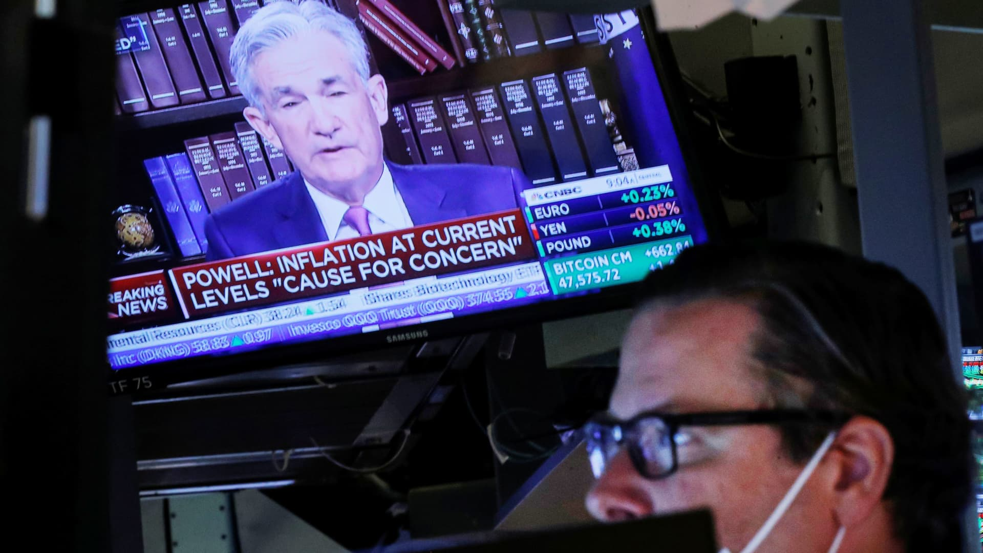 A screen shows Federal Reserve Chair Jerome Powell speak as a trader works inside a post on the floor of the New York Stock Exchange (NYSE), August 27, 2021.