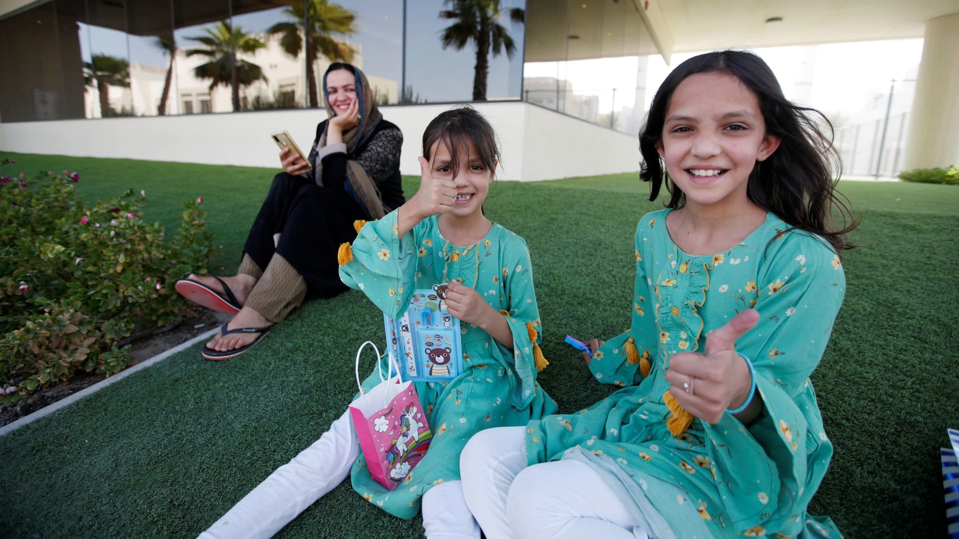Children of Afghan evacuees give a thumbs-up as they play in a park along with their mother at a temporary residence compound in Doha, Qatar, Aug. 27, 2021.