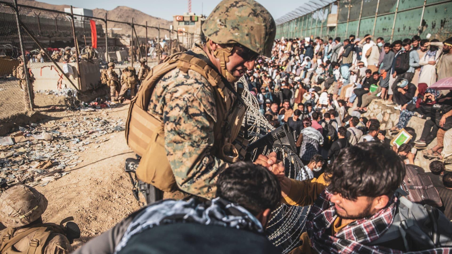 A U.S. Marine assists at an Evacuation Control Check Point (ECC) during an evacuation at Hamid Karzai International Airport, Kabul, Afghanistan, August 26, 2021.