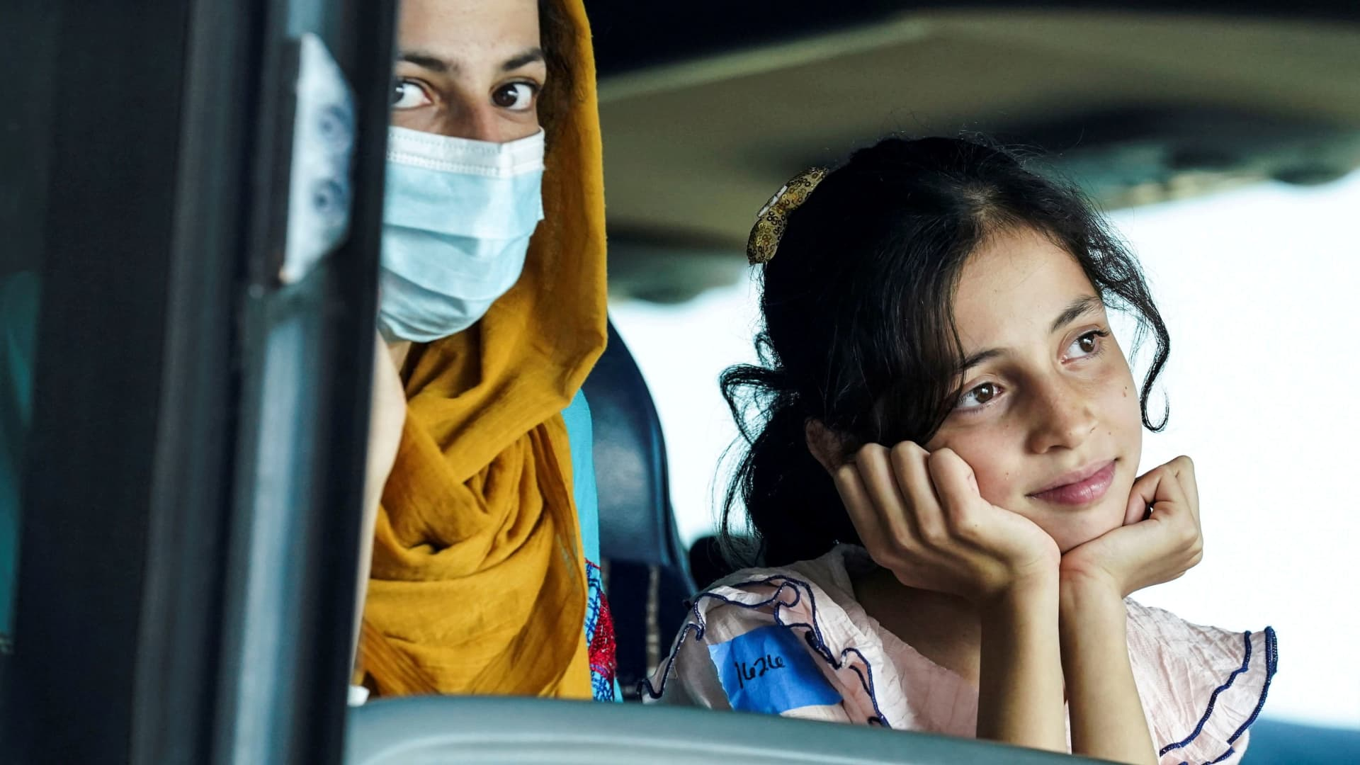 Afghan refugees ride a bus to a processing center at Dulles International Airport on Aug. 25, 2021.