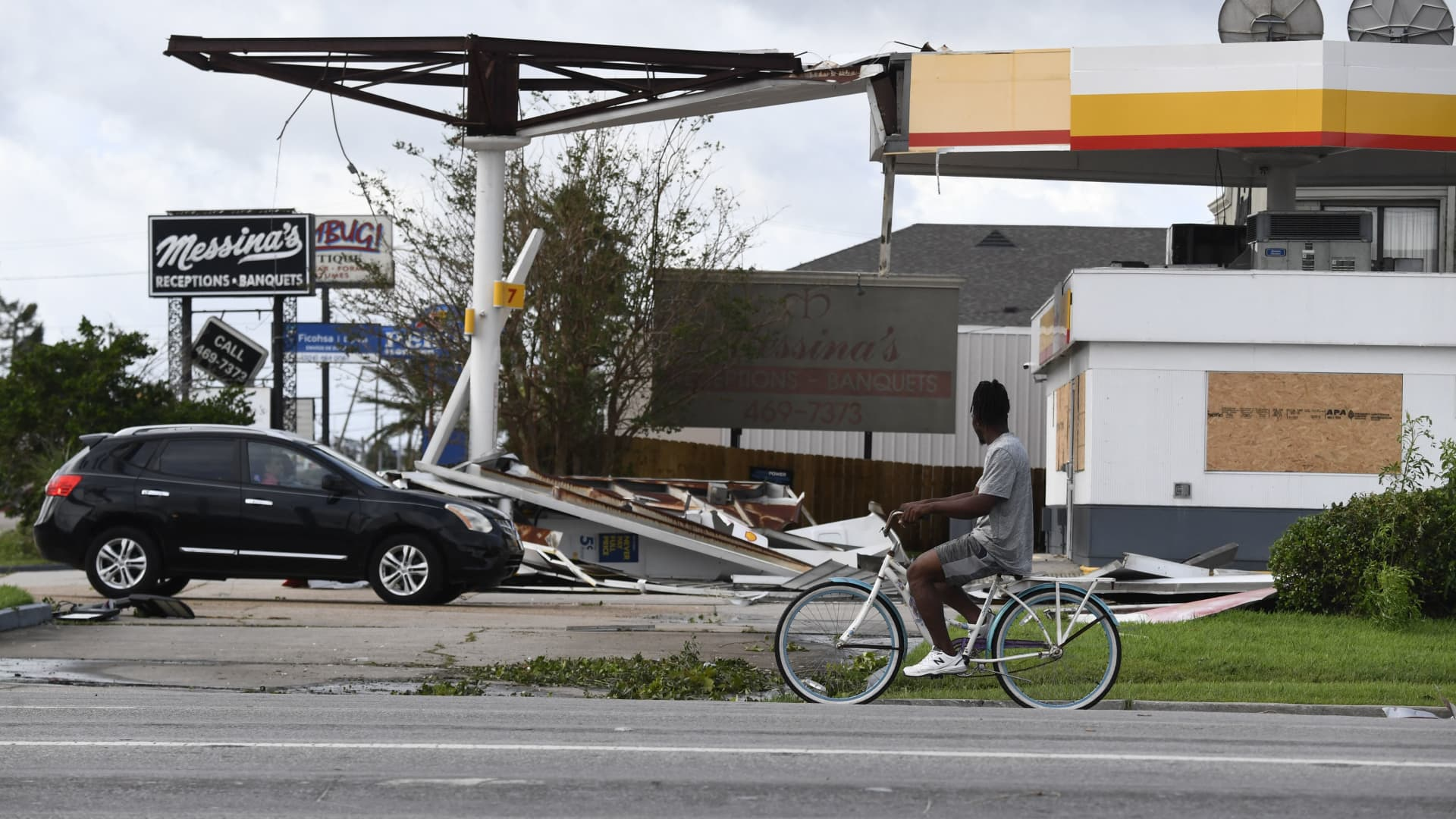 A person on a bicycle passes a damaged Shell station in Kenner, Louisiana, on August 30, 2021 after Hurricane Ida made landfall.
