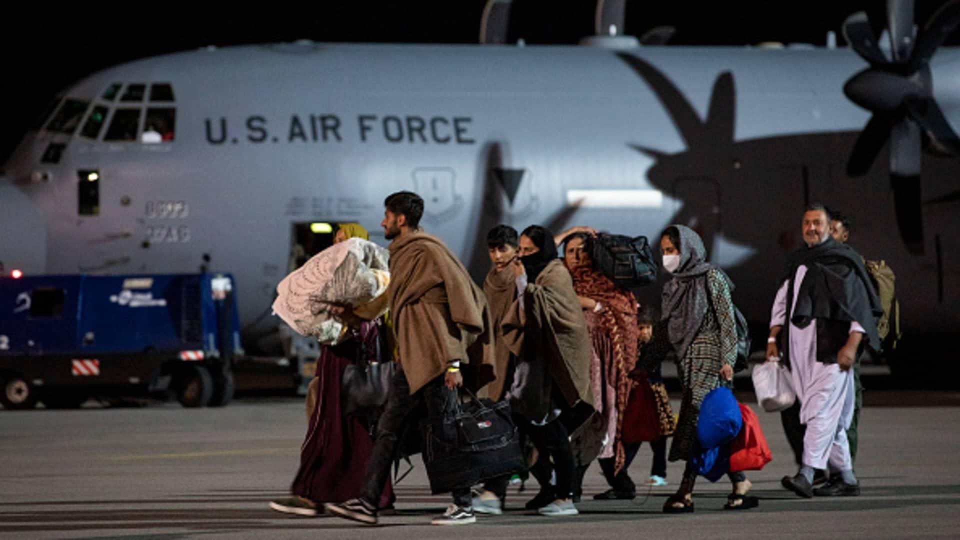 Afghan evacuees arrive at Pristina International Airport in Pristina, Kosovo, via a U.S. Air Force cargo plane, on Aug. 29, 2021.