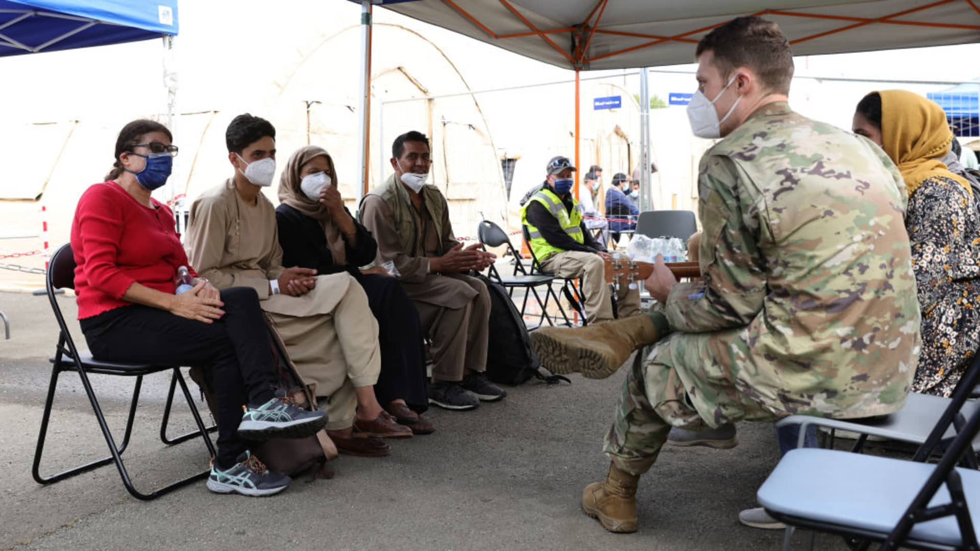 A U.S. military officer plays a ukulele for evacuees from Afghanistan at a waiting area at Ramstein Air Base in Germany on Aug. 26, 2021.