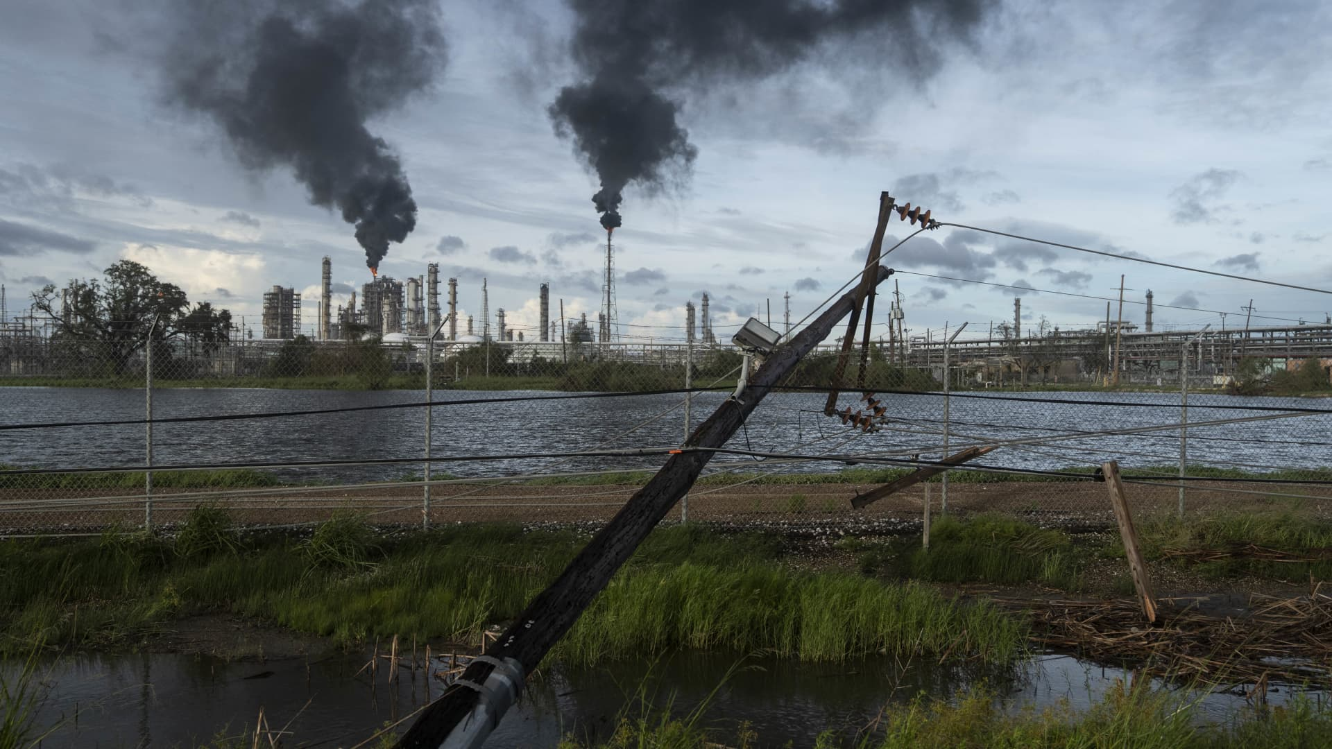 Broken power lines, destroyed by Hurricane Ida, are seen along a highway near a petroleum refinery on August 30, 2021 outside LaPlace, Louisiana.