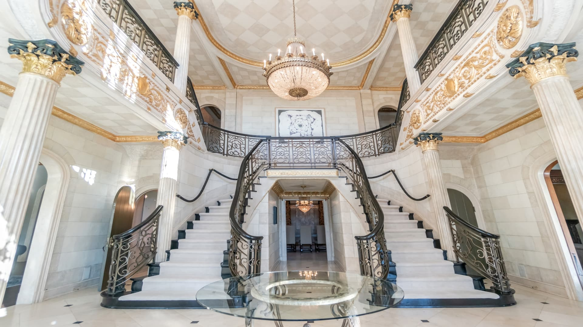 The guilded entry way includes ornate columns, gold trim and a double staircase.