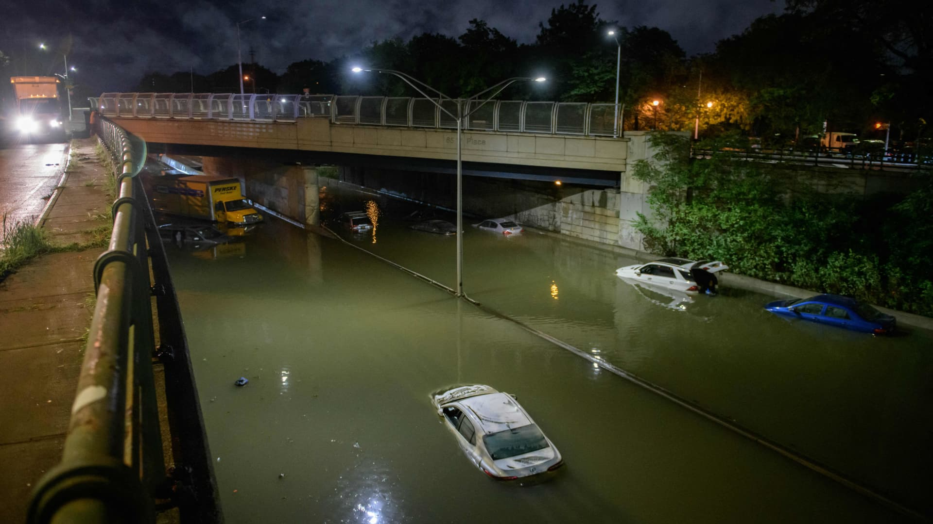 Floodwater surrounds vehicles following heavy rain on an expressway in Brooklyn, New York.