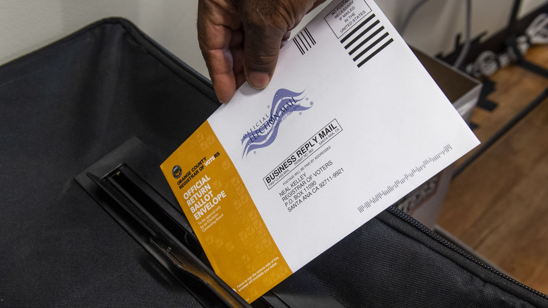 A poll worker puts a mail-in ballot in a security box in the recall election of Gov. Gavin Newsom at a center in San Clemente, CA on Tuesday, September 7, 2021.