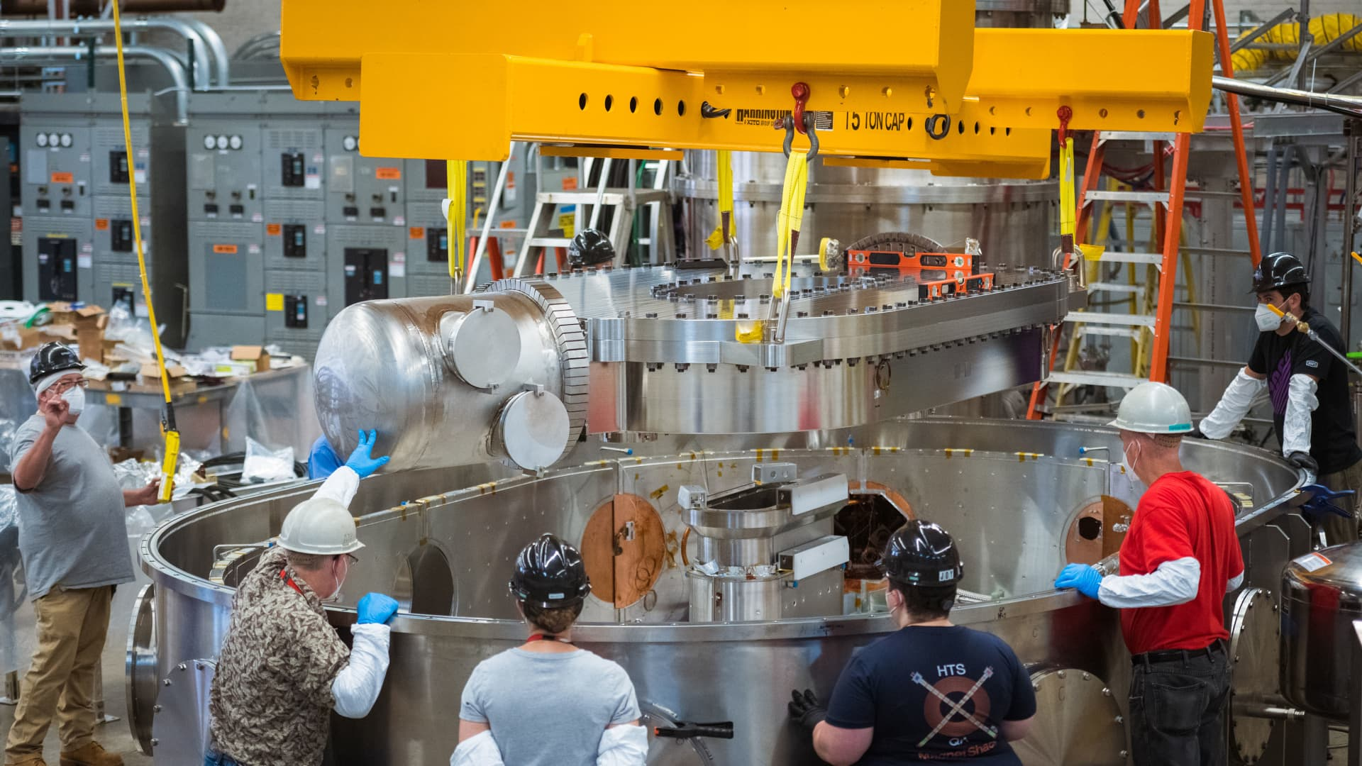 Team members from CFS and MIT here are lowering the superconducting magnet into the test stand.