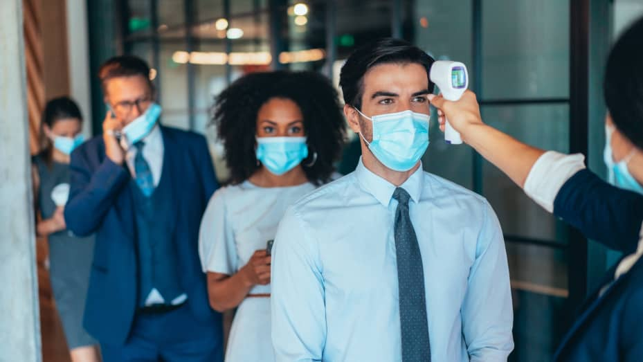 Business colleagues with protective face masks using infrared thermometer for measuring temperature before entrance in office.